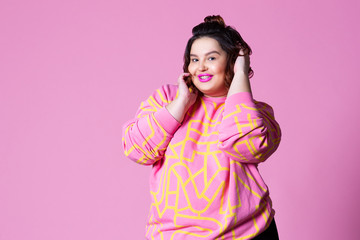 Happy plus size model in casual clothes, fat woman on pink background