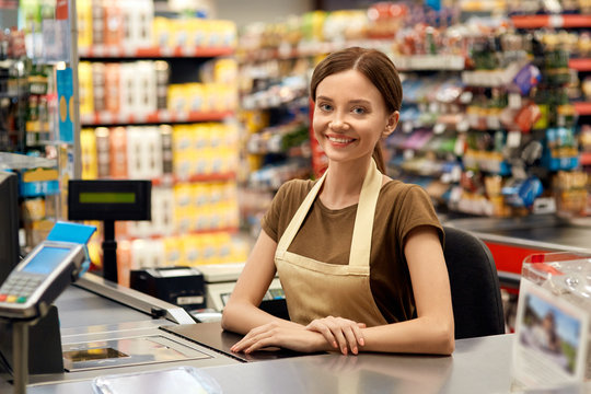 Young adult woman cashier on checkout in market