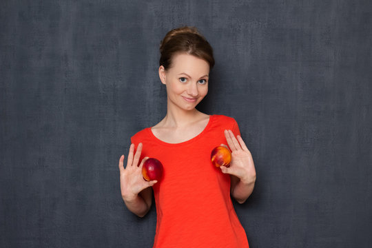 Portrait of happy young woman holding nectarines in hands over chest
