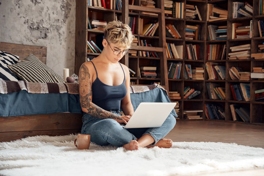 Side Hustle. Young woman short hair in glasses sitting on floor working online on laptop concentrated with cup of coffee