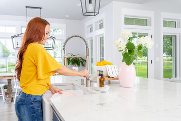 A woman washing dishes in a modern farmhouse kitchen.