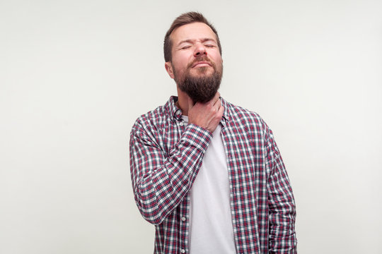 Flu symptoms. Portrait of sick bearded man in casual plaid shirt touching neck suffering sore throat, hard to swallow, closing eyes in grimace of intense pain. studio shot isolated on white background