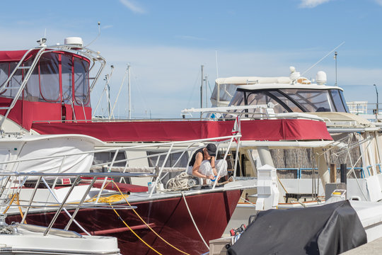 Woman working on docked boat in a yacht basin on a warm sunny day