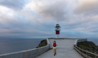 A hiker with a backpack approaches the Cabo Ortegal lighthouse in Galicia in northern Spain. It is half an hour after sunset. Beautiful colorful clouds can be seen in the sky.