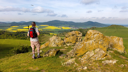 A hiker with a backpack near the city of Kassel on a mountain. The stones have the name Helfensteine. Below is an airfield for gliders. Rape fields bloom in the distance.