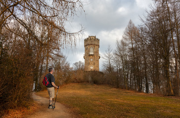 A hiker with a backpack near the city of Kassel in Wilhelmsthal. There is an old tower on the way. It is afternoon on a sunny spring day with warm colors.