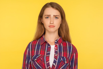 Portrait of unhappy ginger girl in checkered shirt frowning and looking at camera with upset dismal expression, feeling insulted, resentful facial emotion. studio shot isolated on yellow background