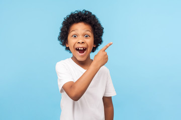 Wow look, advertise here! Portrait of amazed cute little boy with curly hair pointing to empty...