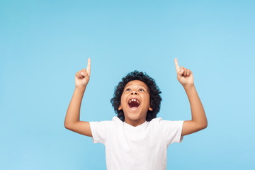 Wow, look up! Portrait of amazed little boy pointing up to empty place on blue background, expressing shock surprise with wide open mouth and showing copy space for advertisement. indoor studio shot