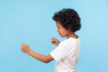 Let's fight! Profile of aggressive little boy with curls in T-shirt holding clenched fists up and looking with furious threatening expression to side. indoor studio shot isolated on blue background