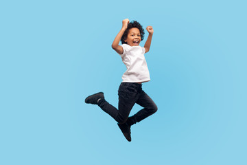 Full length, lively energetic little boy in T-shirt and denim jumping in air screaming with happiness, child flying up, feeling inspired crazy and overjoyed. indoor studio shot, blue background