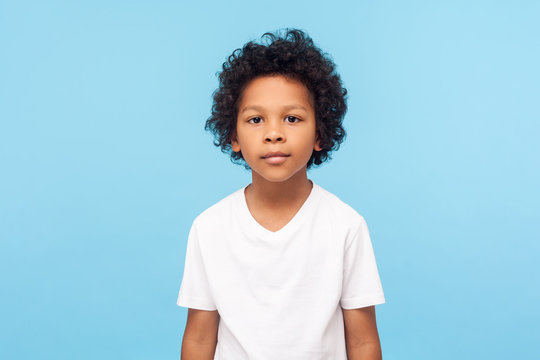 Portrait of cute little boy with stylish curly hairdo in white T-shirt standing, looking at camera with serious attentive face, calm pensive expression. indoor studio shot isolated on blue background