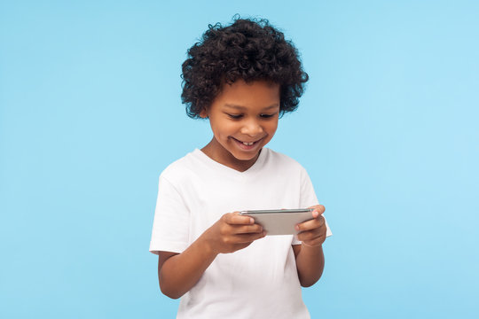 Children entertainment and technology. Happy excited cute little boy with curly hair using mobile phone and smiling, pleased kid playing video game on cellphone, chatting in social network. indoor