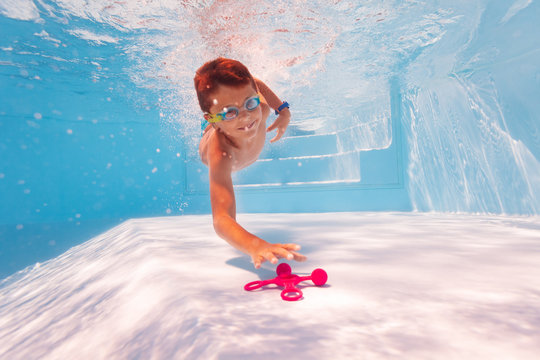 Little happy child dive deep to reach the toy swimming underwater in the pool wearing googles