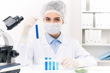 Young female laboratory worker working with liquid substances in flasks