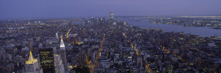 Fototapete - This is the north to south view of New York City from the Empire State Building. The lights of the skyscrapers are on as it dusk.