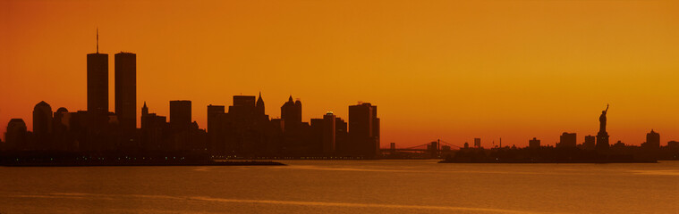 This is the Manhattan skyline from New Jersey. It shows the Statue of Liberty on the right, the world Trade Towers on the left and the skyline in silhouette at sunrise.