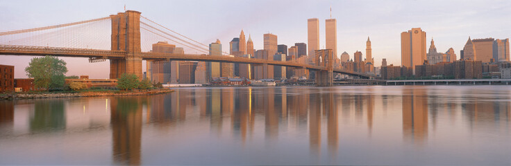 Spoed Fotobehang Brooklyn Bridge This is the Brooklyn Bridge over the East River. The Manhattan skyline is behind it at sunrise. The East River shows a reflection of the skyline.