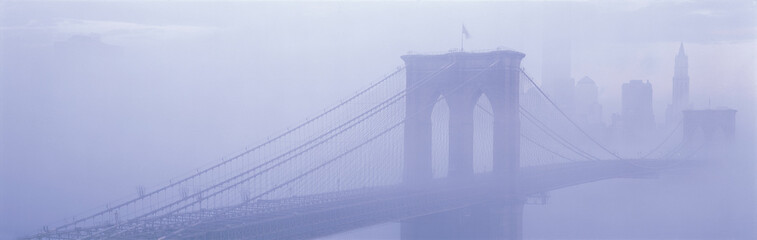This is the Brooklyn Bridge over the East River. There is a morning Fog enveloping the bridge and city, causing Manhattan to look like the Emerald City in the Land of Oz.