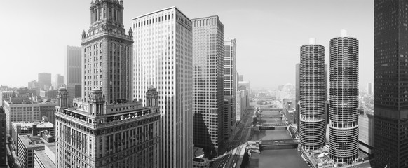 This is a view looking over the Chicago River. The Marina Tower Apartments, the Wrigley Building and the skyline surround the river. It is a black and white shot.