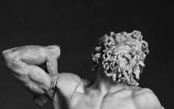 Black and white closeup photo of classical roman statue of man with a suffering face