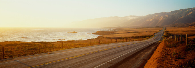 Foto auf Leinwand Weiß This is Route 1also known as the Pacific Coast Highway. The road is situated next to the ocean with the mountains in the distance. The road goes off into infinity into the sunset.