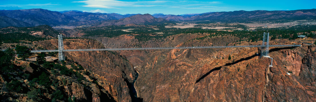 This is the Royal Gorge Bridge which is the world's highest suspension bridge. It is 1053 Ft. above the Arkansas River. Mountains are in the background with red rock below the bridge.