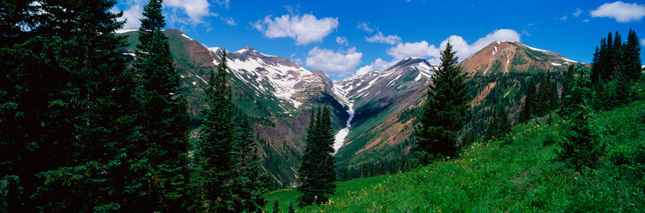 This is an image of the Rocky Mountains in the summer. There is a small amount of snow on the mountains and the green grass of summer in the fields. The sky is blue with white puffy clouds.