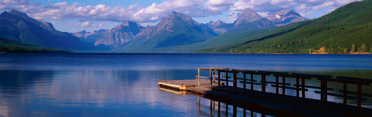 Wall Mural - This is a boat dock at Lake McDonald. The blue water of the lake surrounds the dock with mountains in the background.