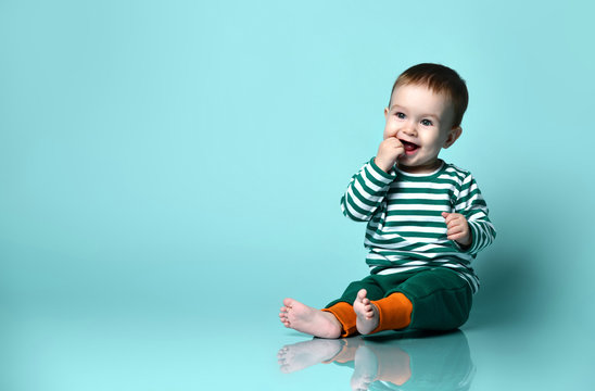 Little baby boy in stylish casual clothing barefoot sitting on floor and smiling over blue wall background
