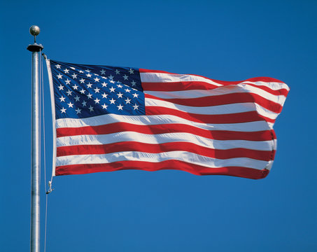 This is an American flag on a flagpole, waving in the wind.