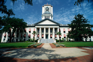 This is the State Capitol building. It has a large concrete stairway leading up to it with large...