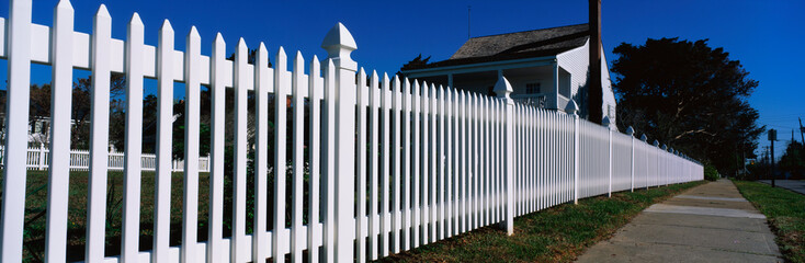 This is a close up of a white picket fence and a typical looking suburban house. We see the sidewalk that runs past it on the right hand side of the image.