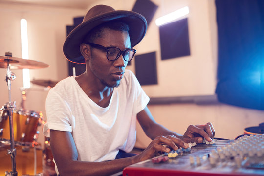 Portrait of young African-American man writing music in recording studio using sound equalizing mixer, copy space