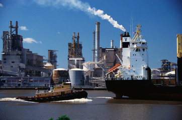 This is a Monrovia cargo ship on the Merkur River and Union Camp Paper Mill loading onto the cargo ship.  It is a paper mill with smokestacks overlooking the river.