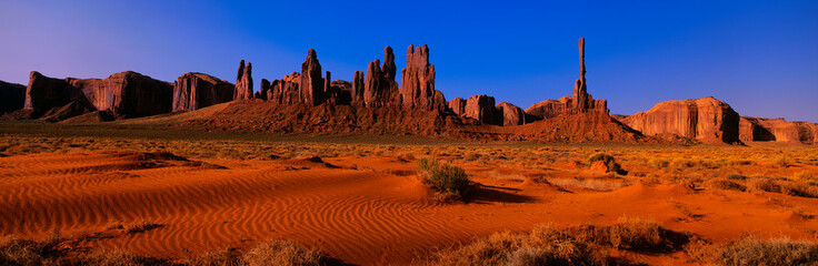 Poster Cuban Red This is Yei Bi Chei and The Totem Pole at sunrise. In front are the sand dunes of Monument Valley.