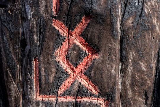 Slavic pagan esoteric symbols (runes) are carved on a wooden surface