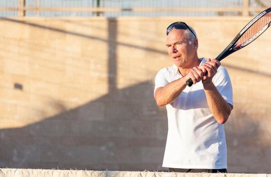Senior man playing tennis on an outdoor court