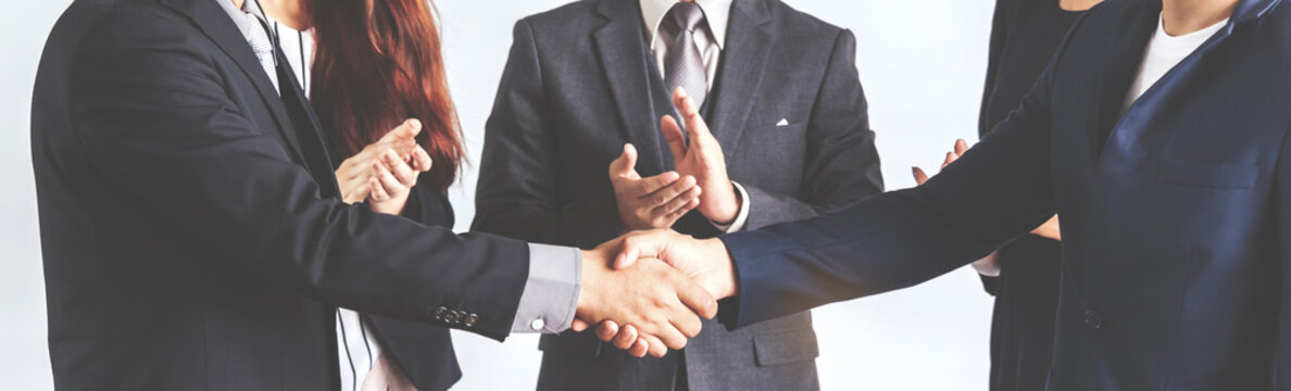 Image two business partners in elegant suit successful handshake together standing in front of group of casual business clapping hands in modern office.Partnership approval and thanks gesture concept