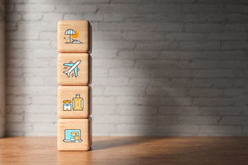 cubes with travel icons on wooden surface in front of a brick wall