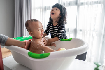cute asian little sister help her baby brother to bath
