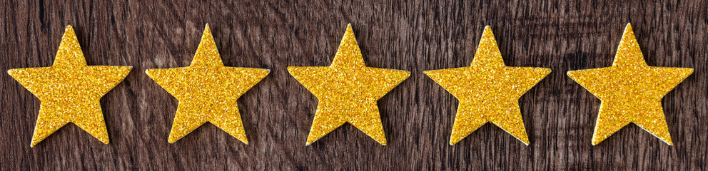 Gold glitter stars in a border on dark wood as a background
