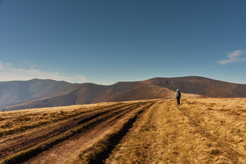 Adorable autumn landscapes in Carpathian mountains with beautiful tourist girl traveling with red tent