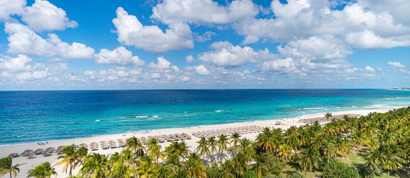 Top view of the Caribbean dream beach in Varadero Cuba with sun lounger and thatched huts. Panoramic view of 20 km long beach of the resort town of Varadero.