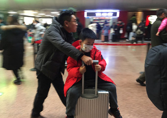A man pushes his luggage as a child sits atop with a mask at the Beijing West Railway Station, in Beijing