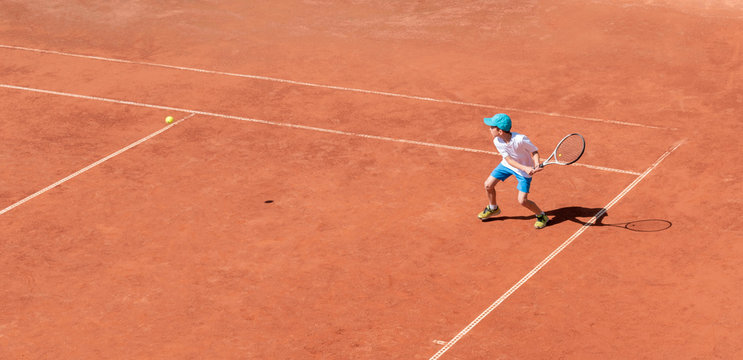 A boy plays tennis on a clay tennis court. The child is concentrated and focused on the game. Individual sport. Determined young athlete. Kids tournament, match. Active sport.
