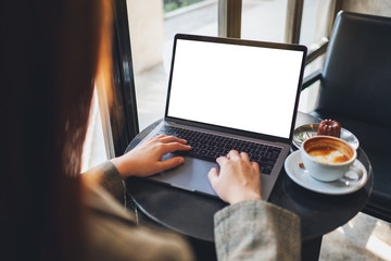 Mockup image of a woman using and typing on laptop computer with blank white desktop screen in cafe