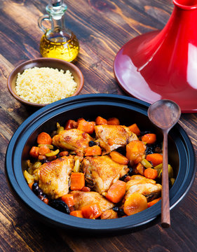 Tagine with cooked chicken and vegetables. Brown wooden background.