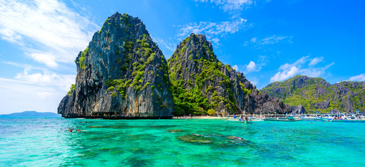 Tropical Shimizu Island and paradise beach, El Nido, Palawan, Philippines. Tour A Route. Coral reef and sharp limestone cliffs.