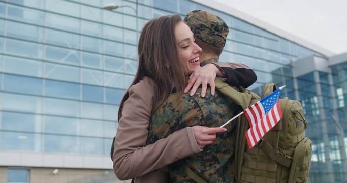 Girl running and cudling military man.